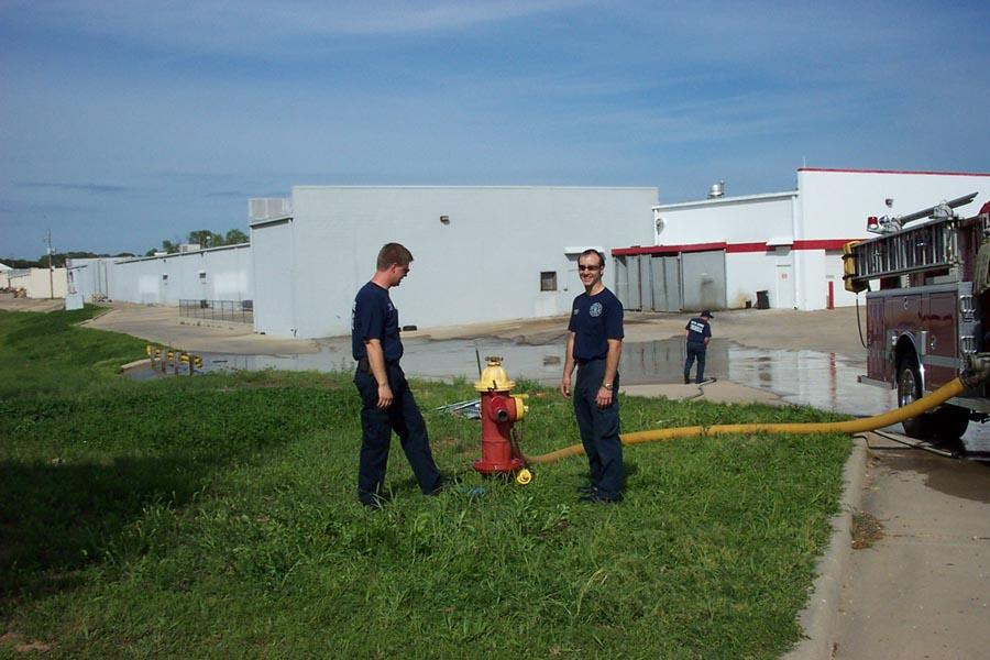 two fire personnel standing next to fire hydrant during training
