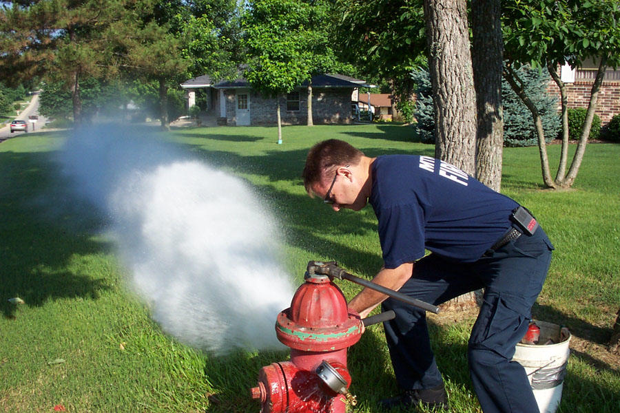water flowing out of hydrant with fire personnel present, during fire hydrant training