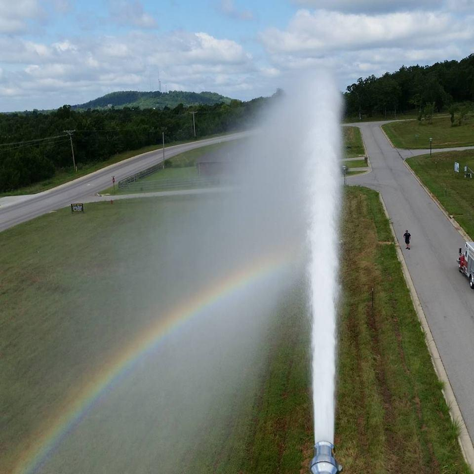 water spraying from fire engine, creating a rainbow in the mist