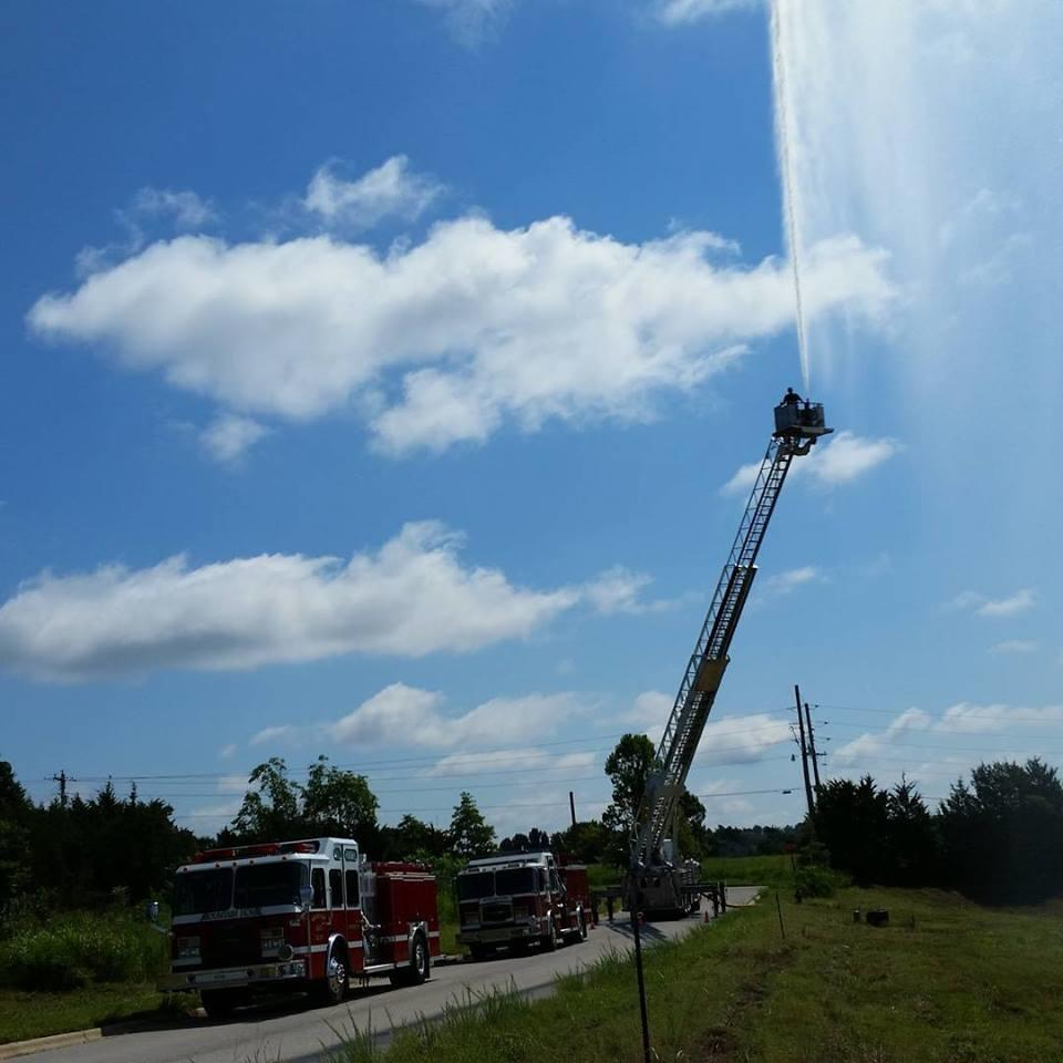 water spraying from top of fire engine ladder during tower truck training