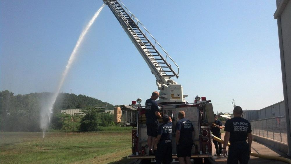 Water pouring from top of fire engine ladder during ladder training