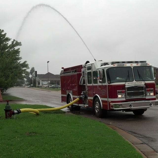 Water spraying in arch from the top of the fire engine during pumper training