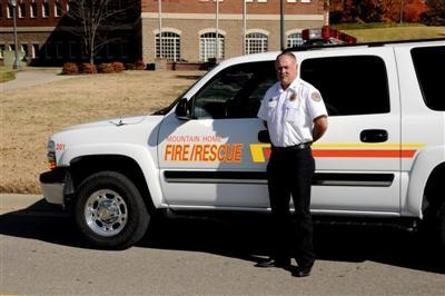 Fire Chief Ken Williams standing in front of Fire Department vehicle